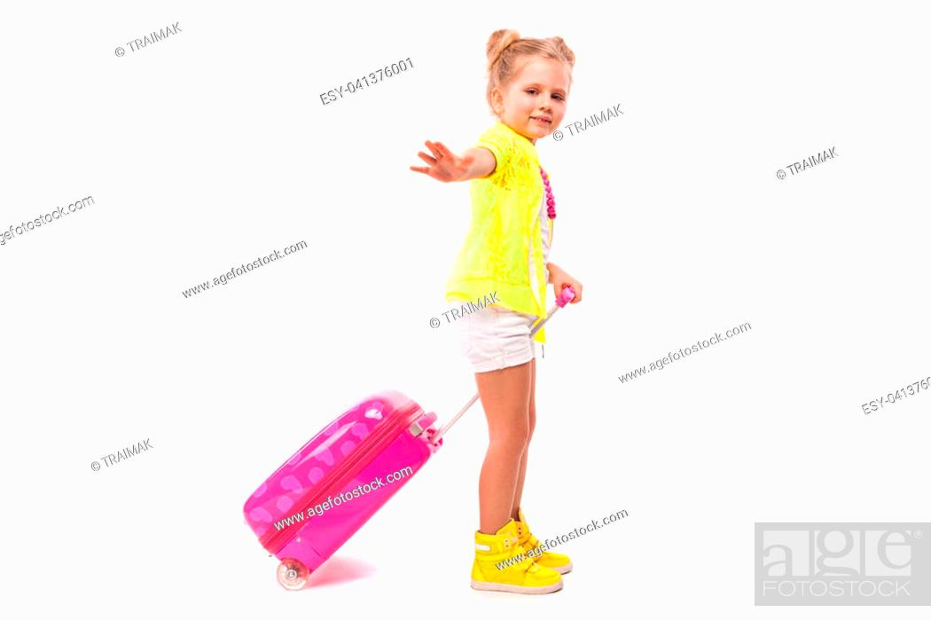 Stock Photo: Isolated on white, cute little caucasian blonde girl in yellow shirt, white shorts, and yellow boots hold pink suitcase by the handle.