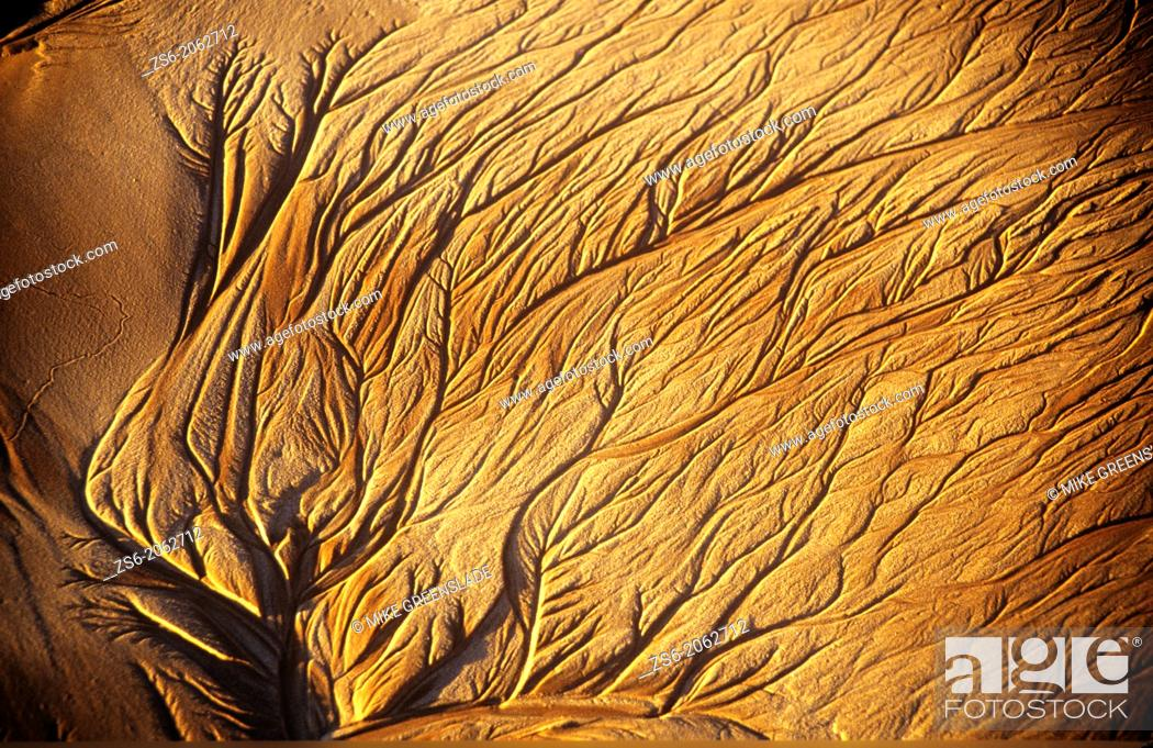 Imagen: Abstract pattern made in the sand, as water drains off the beach at sunset in Broome, Western Australia.