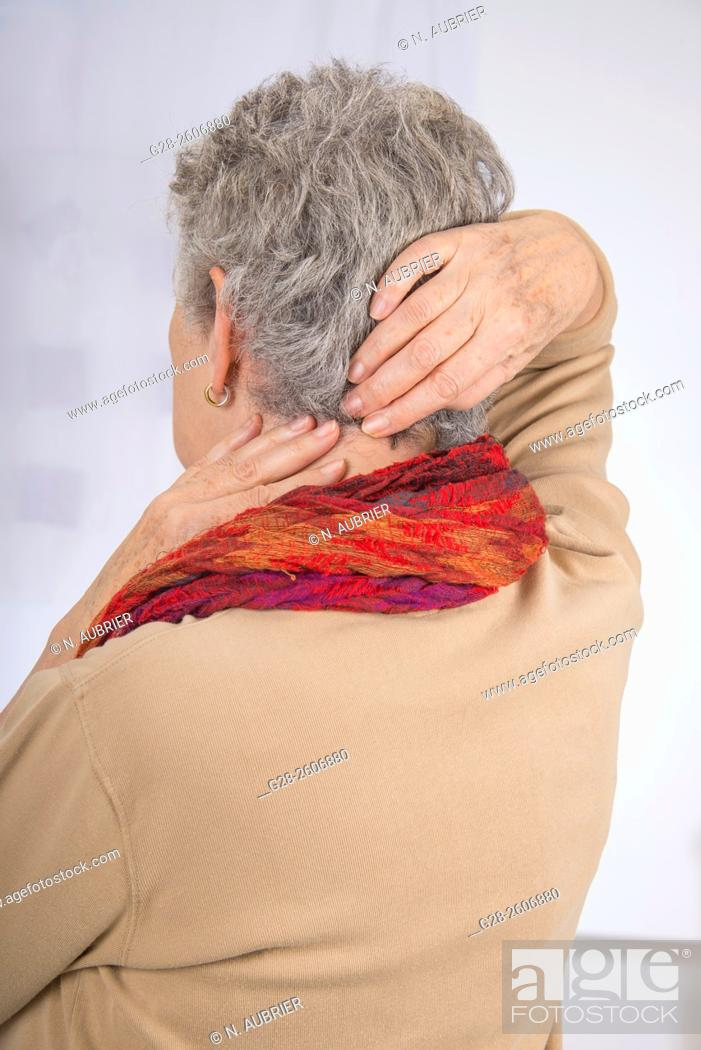 Stock Photo: Senior woman with grey hair, seen from behind, suffering from a neck pain, trying to relieve pain by massaging her back.