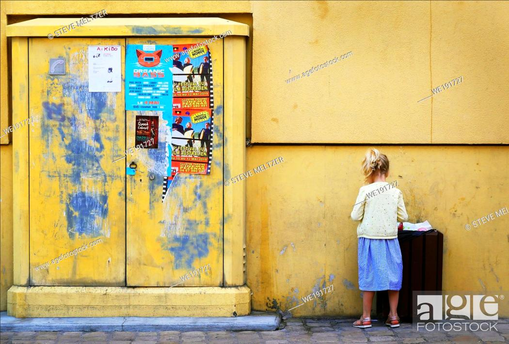 Stock Photo: A little girl stands by a yellow wall.