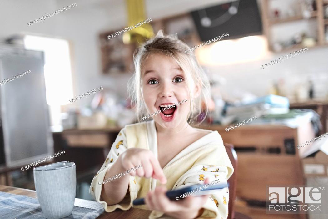 Stock Photo: Portrait of excited little girl in the kitchen pointing at smartphone.