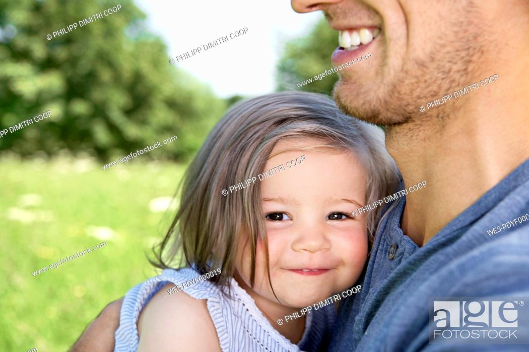 Stock Photo: Gemany, Cologne, Father and daughter smiling, close up.
