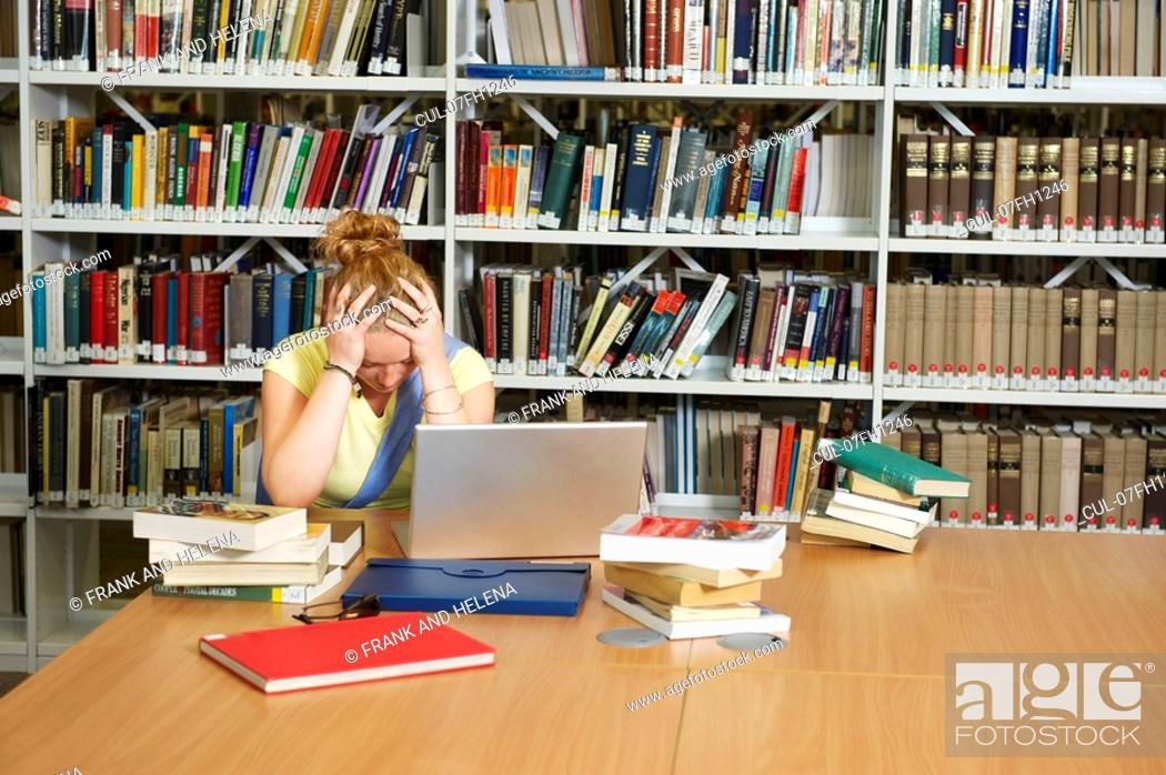 Stock Photo: Despairing young woman in library.