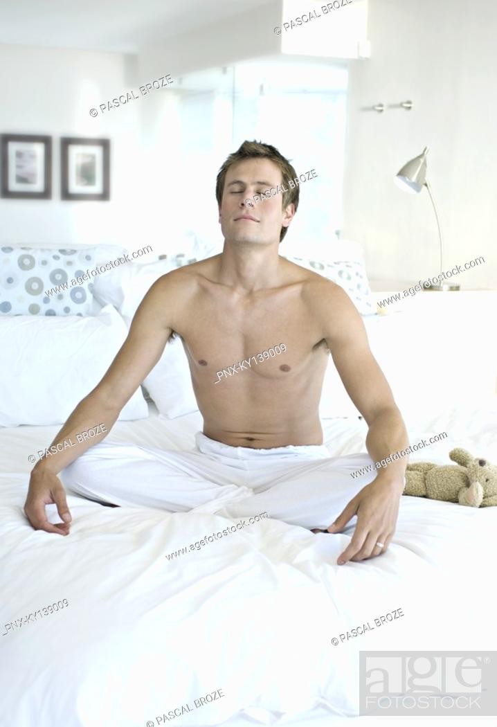 Stock Photo: Young man in yoga attitude, indoors.