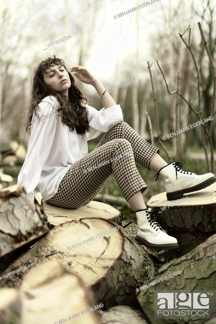 Stock Photo: Young woman sitting on tree stump. Berlin, Germany.
