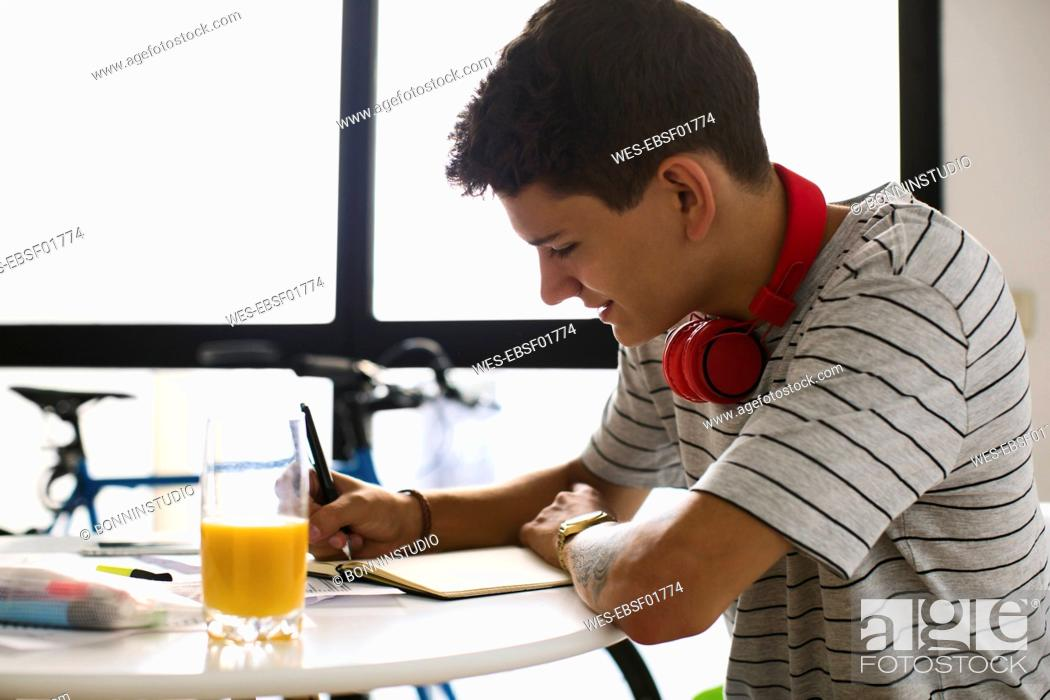 Stock Photo: Teenage boy doing homeworks.
