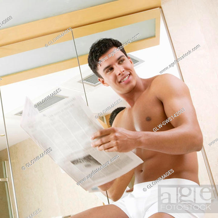 Stock Photo: Low angle view of a young man sitting in the bathroom holding a newspaper.