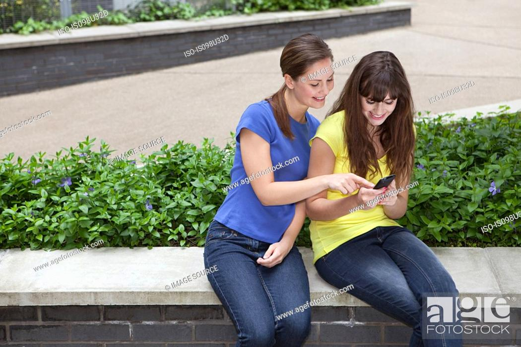 Stock Photo: Friends using smartphone.