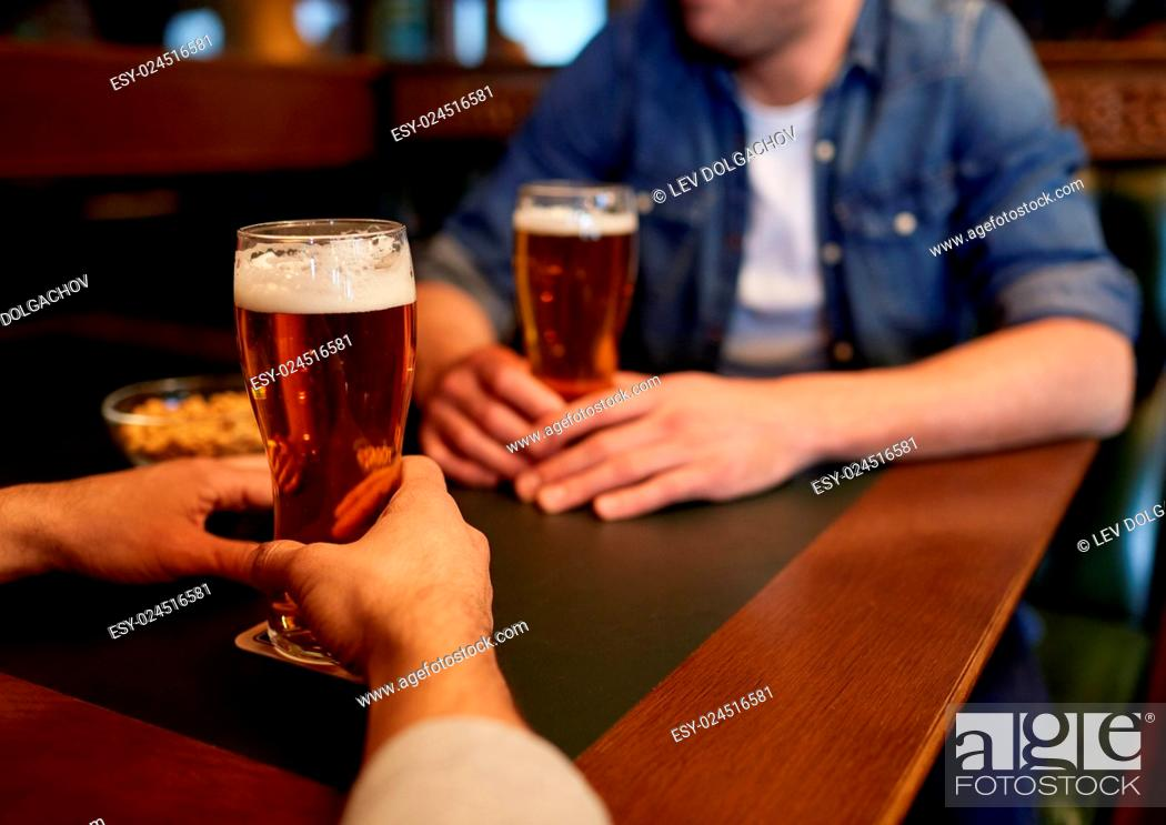 Stock Photo: people, men, leisure, friendship and communication concept - close up of male friends drinking draft beer at bar or pub.