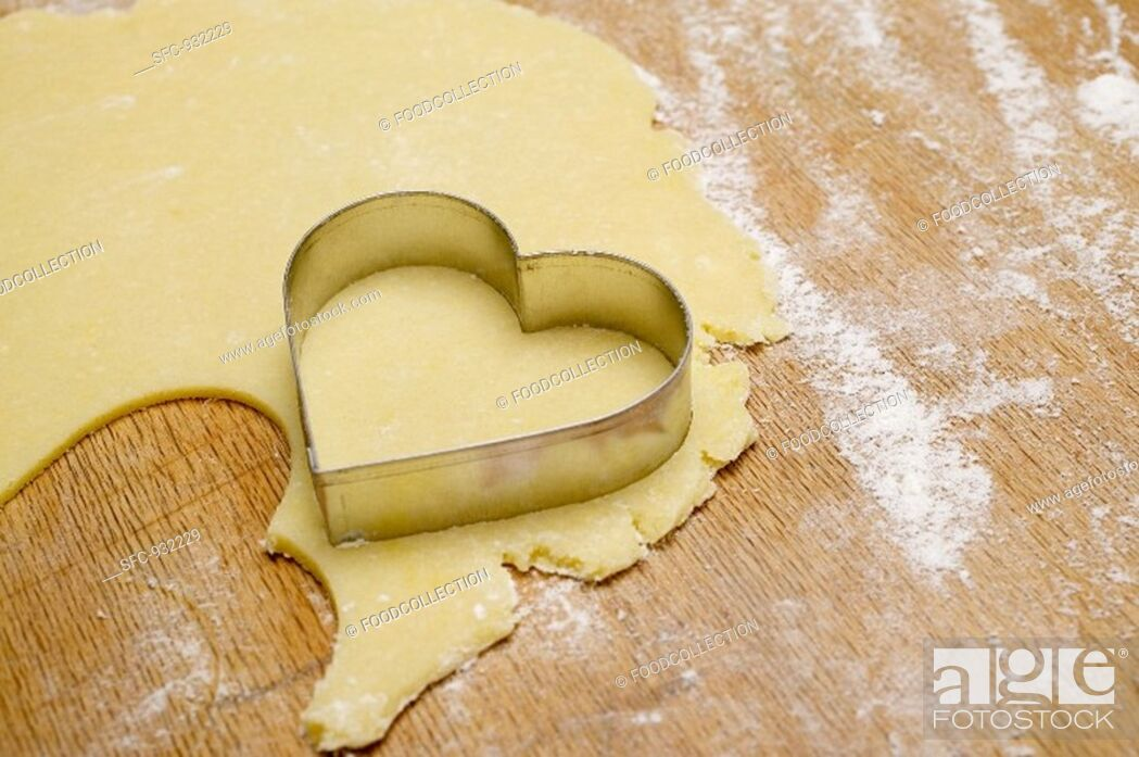 Stock Photo: Cutting out a heart-shaped biscuit.