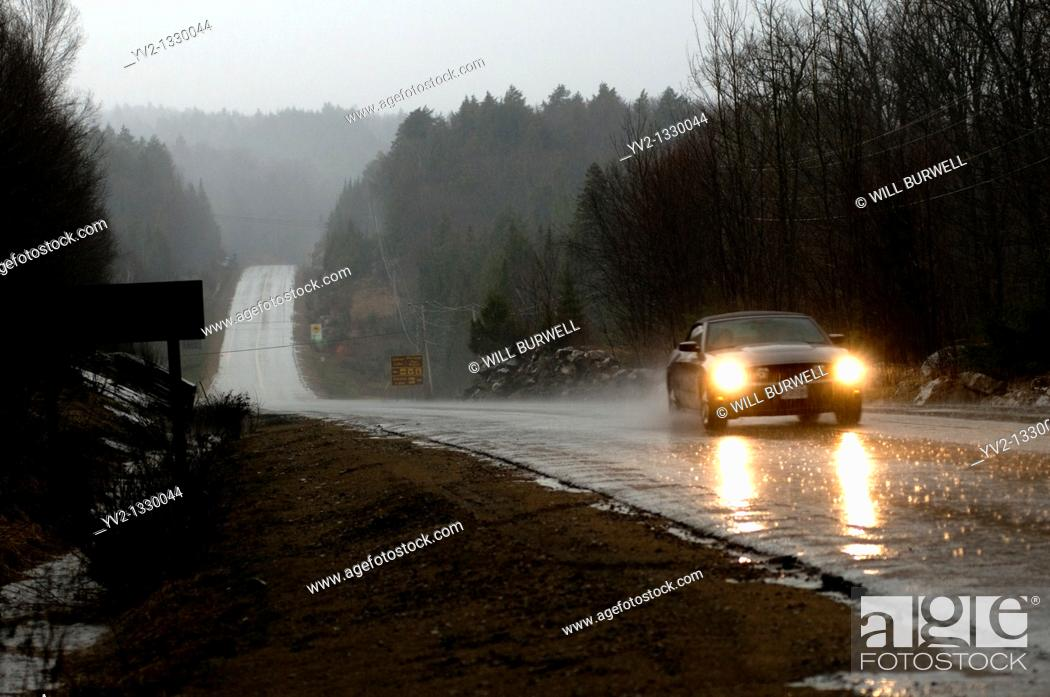 Stock Photo: Car driving through a down pour, Algonquin Park, Ontario, Canada.