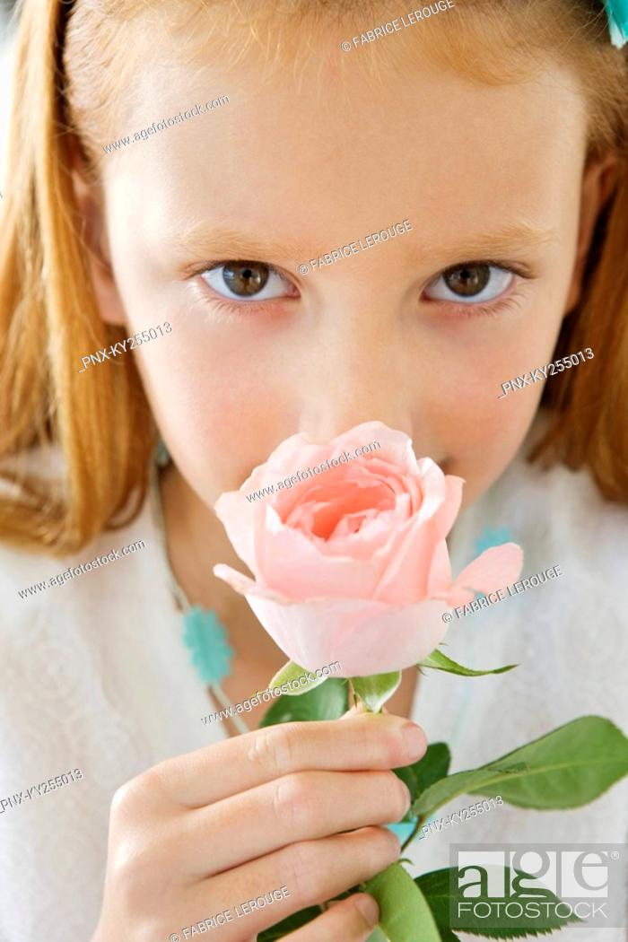 Stock Photo: Close-up of a flower girl smelling a flower.