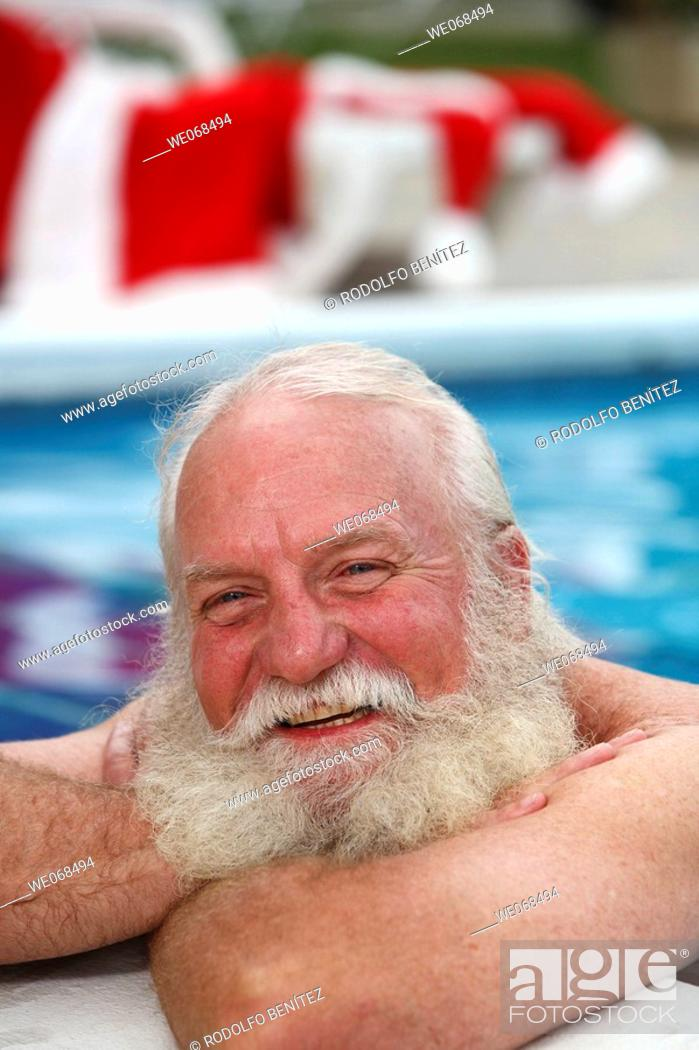 Stock Photo: Santa smiles on the side of a swimming pool.
