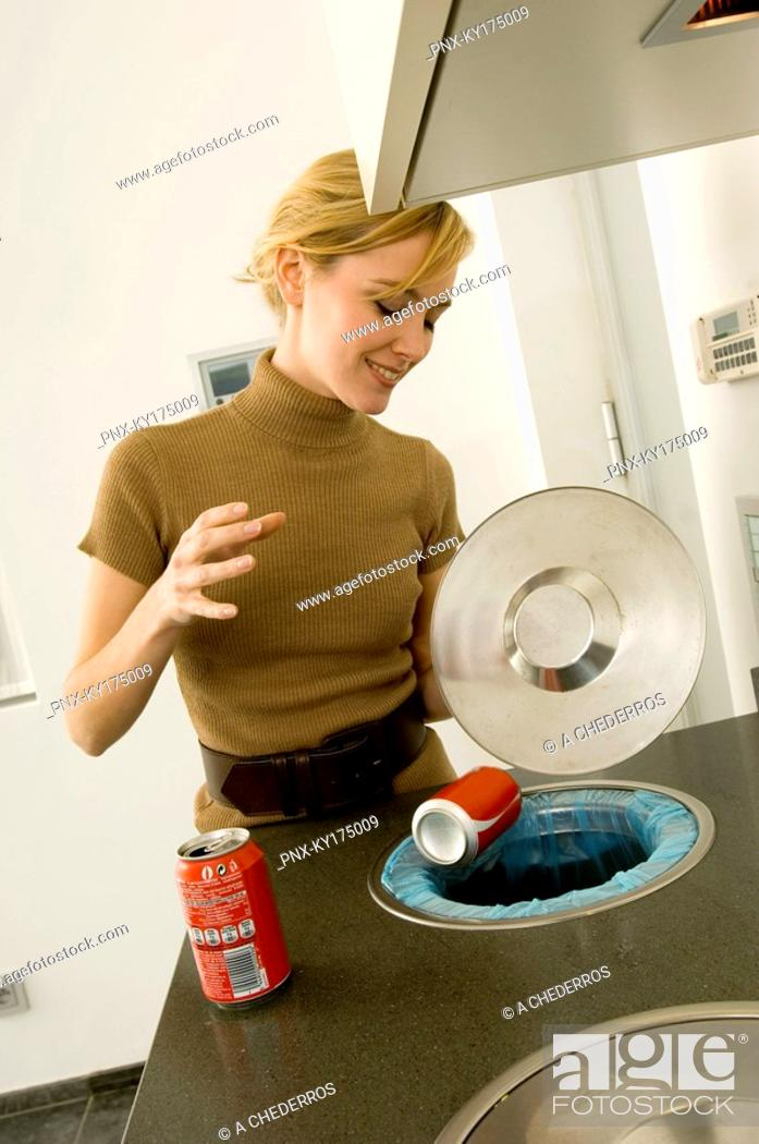 Stock Photo: Young woman putting a drink can into a garbage bin.