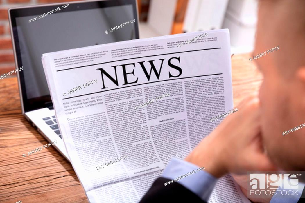 Stock Photo: Close-up Of A Man's Hand Holding Newspaper Over Wooden Desk.