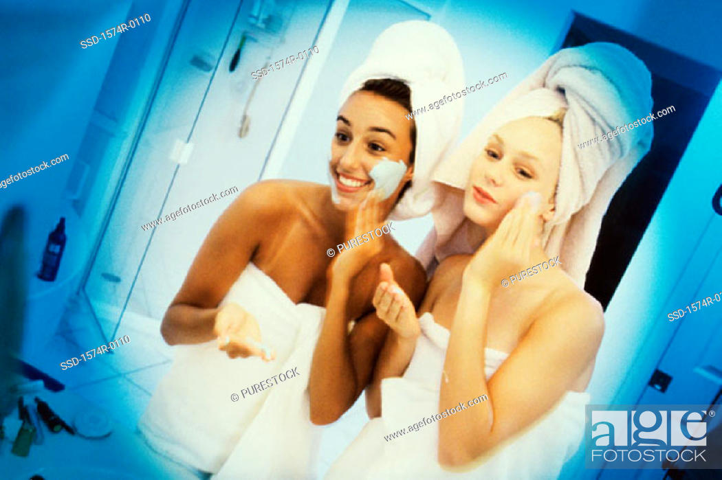 Stock Photo: Two women wrapped in towels applying lotion.