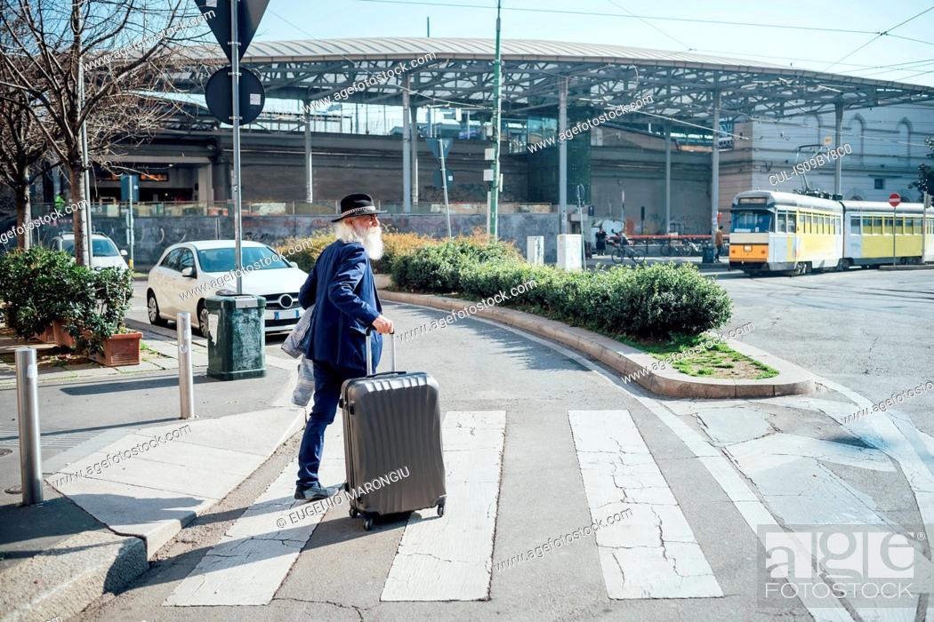 Stock Photo: Senior businessman with wheeled luggage walking on pedestrian crossing, Milano, Lombardia, Italy.