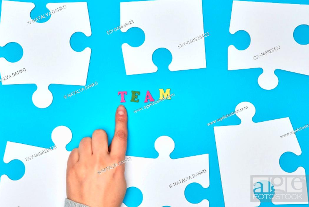 Stock Photo: white big puzzles on a blue background, inscription team, the concept of recruitment in the company.