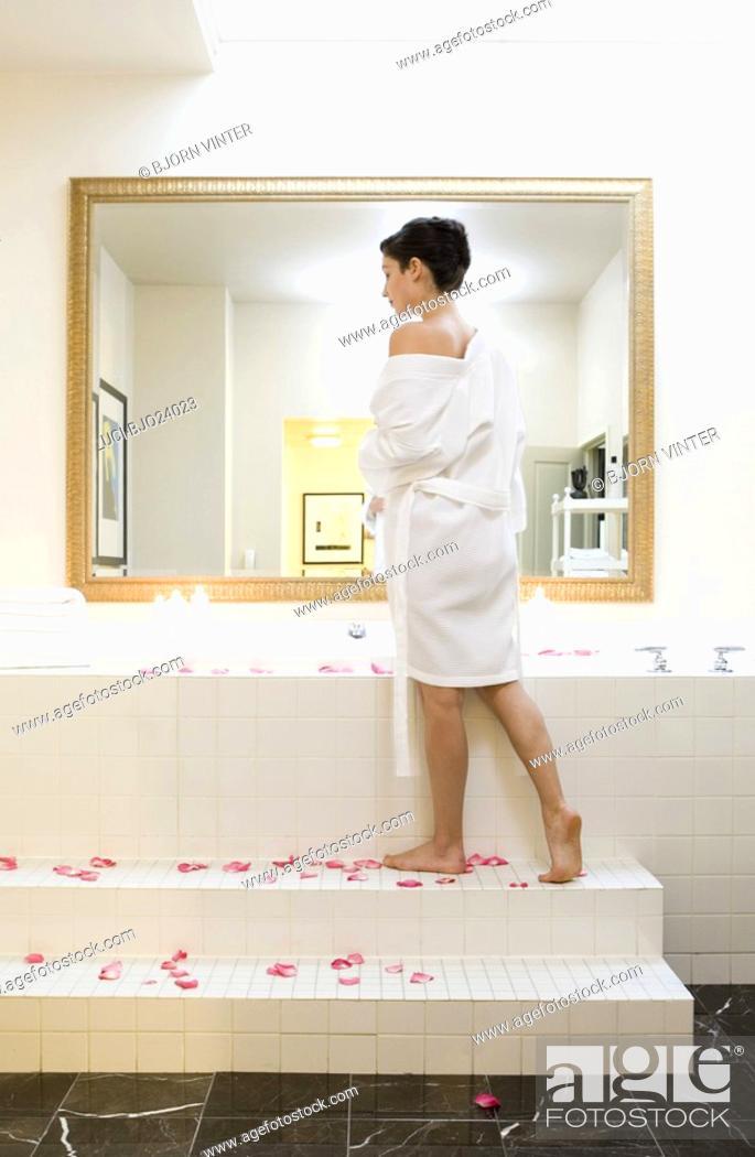 Stock Photo: Woman standing next to bubble bath.