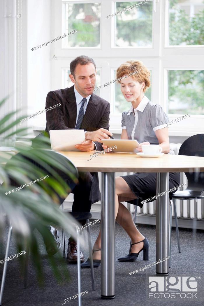 Stock Photo: A businessman and businesswoman using a digital tablet in a meeting.