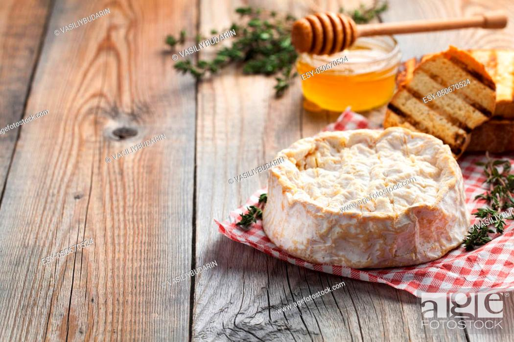 Stock Photo: A real Camembert from France with thyme, honey and toasted bread on old wooden rustic table. Soft cheese on a wooden background with copy space.