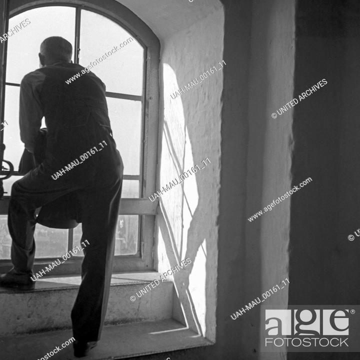 Stock Photo: Ein Mann genießt den Ausblick auf die Stadt aus einem Turmfenster der Frauenkirche in München, Deutschland 1930er Jahre. A man enjoying the view over the city.
