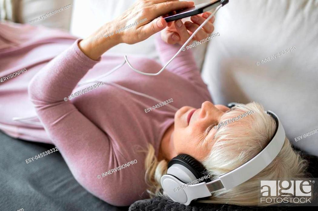 Stock Photo: Portrait of glad senior lady lying on couch listening music on mobile.
