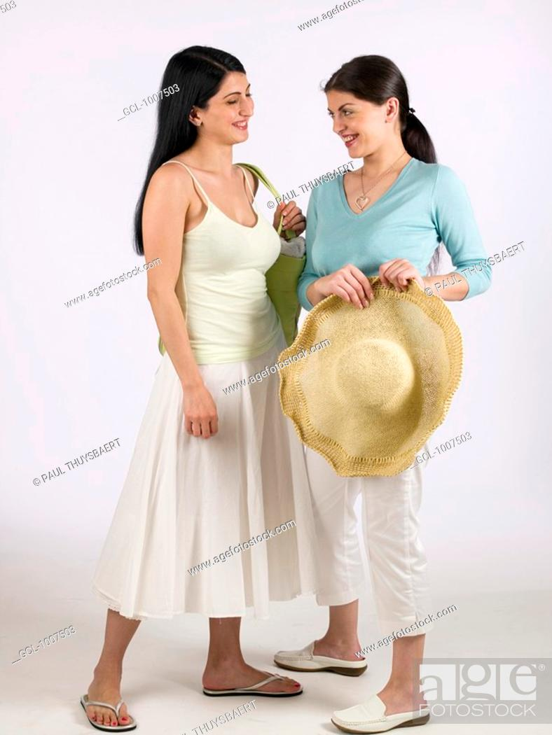 Stock Photo: Two women with holding a sunhat and laughing.