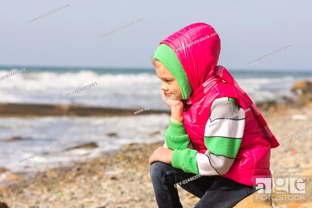 Imagen: Girl sitting on the rocky beach and the sea head on his hand looking to the frame.