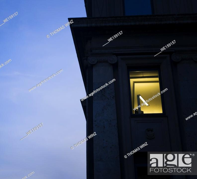 Stock Photo: Old office building with a lamp on at dusk , Stuttgart , Germany.