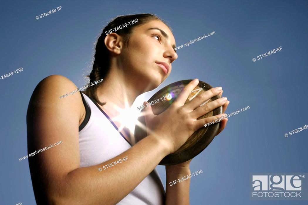 Stock Photo: Woman holding a discus in her hands.