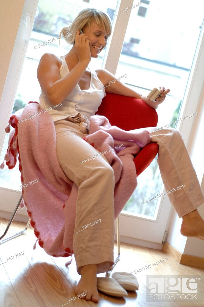 Stock Photo: Relaxed young woman on the phone at home.