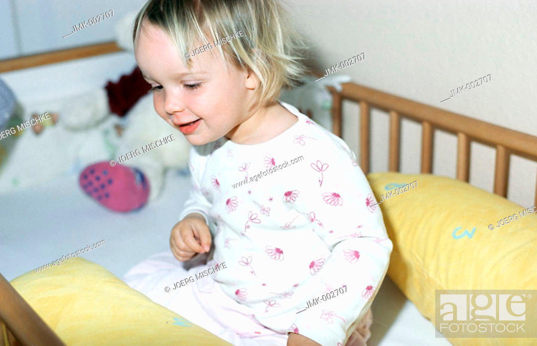 Stock Photo: A little girl, 1-5 years old, sitting in it's bed.