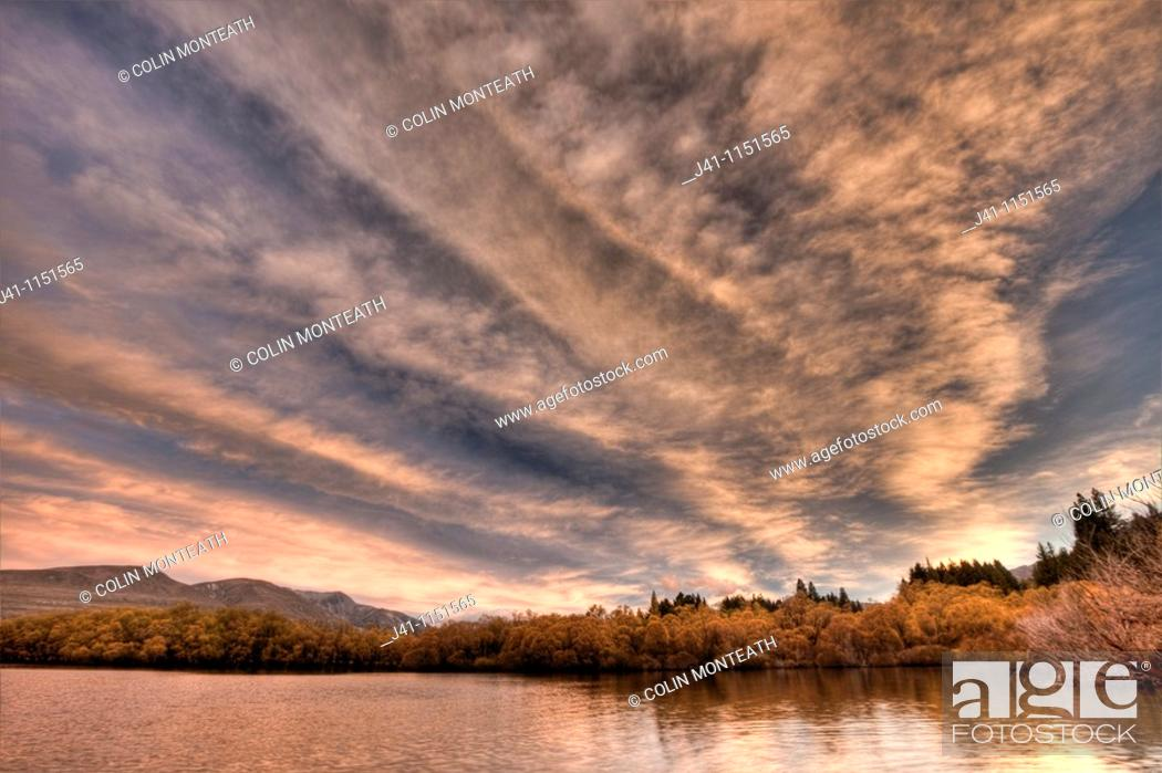 Stock Photo: Frontal weather system from SW moves high over Lake Heron sheep & cattle station at dawn, autumn, Canterbury.