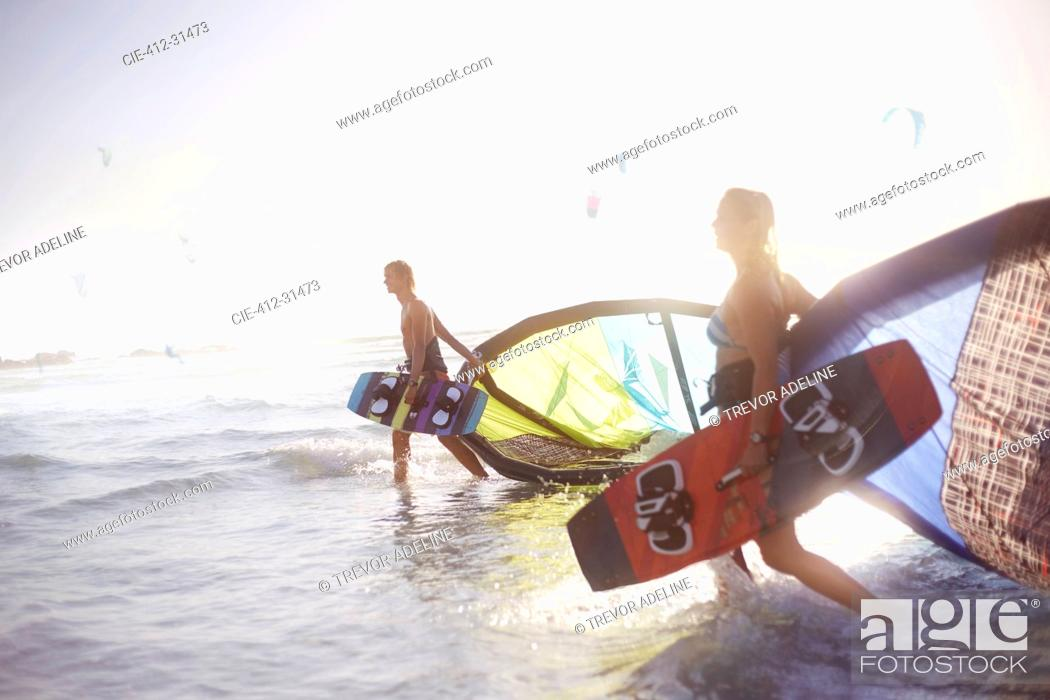Imagen: Couple walking into surf with kiteboard equipment.