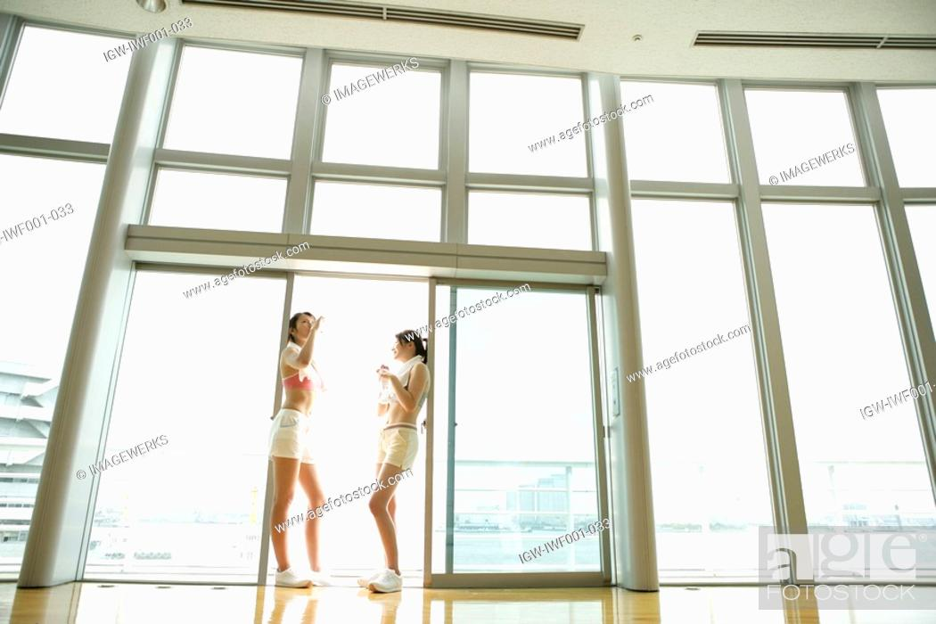 Stock Photo: Two young women take a break from exercise as they drink water while standing near the sliding door.