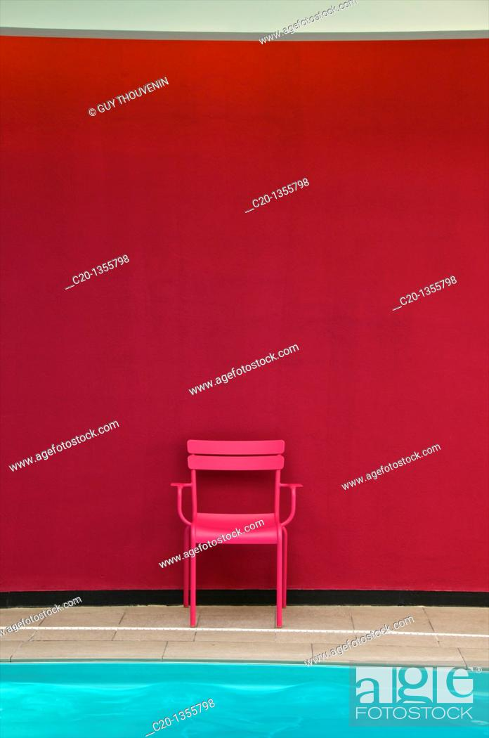 Stock Photo: Pink metal chair and blue water of indoor swimming pool Best Western Hotel Reims Marne 51 France.