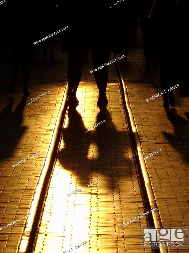 Stock Photo: Szewska street with people and their shadows at sunset, Krakow, Poland.