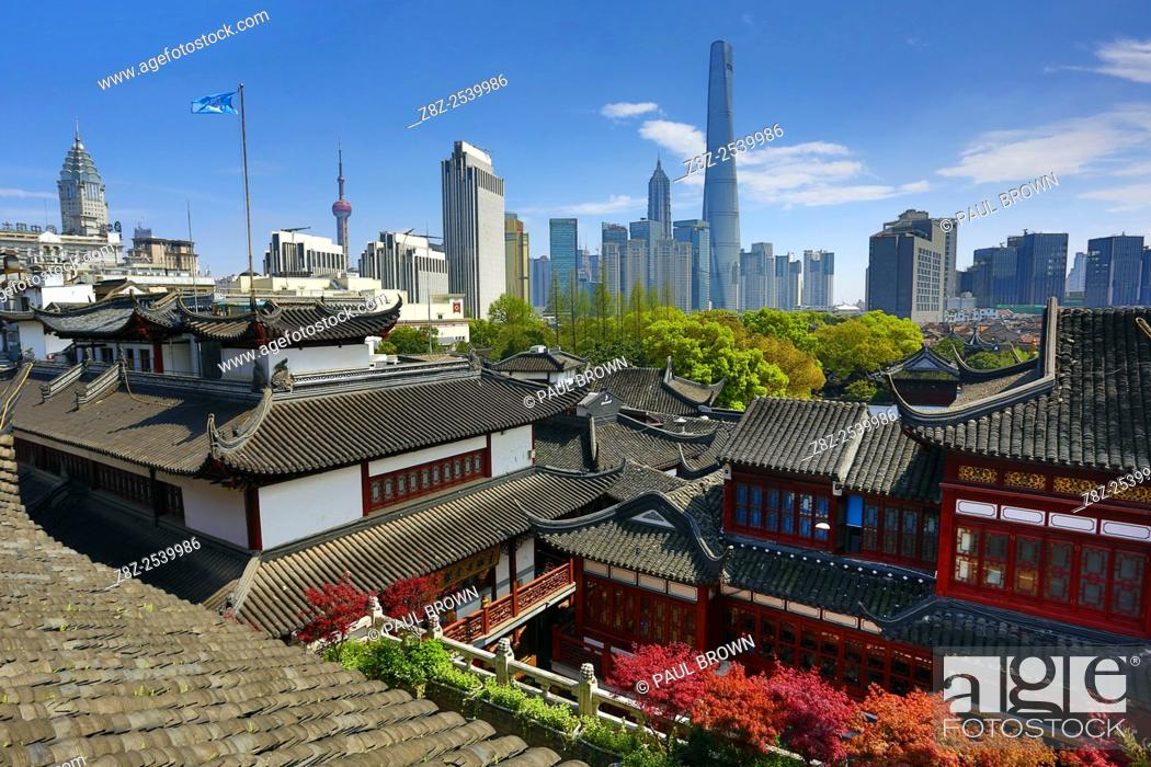 Stock Photo: The Pudong new city skyline in Shangha in the background of the Yuyuan gardens in the Old City, Shanghai, China.