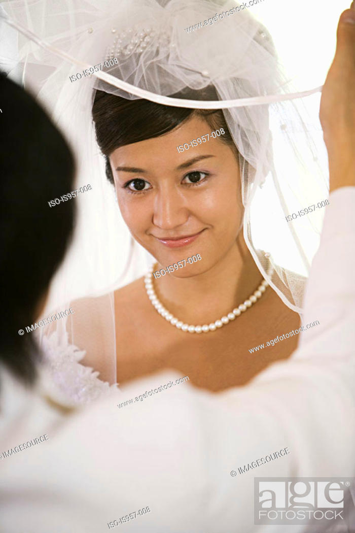 Stock Photo: Groom lifting bridal veil.