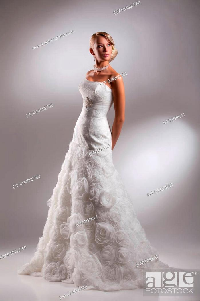 Young Beautiful Blonde Woman In A Wedding Dress On A Studio