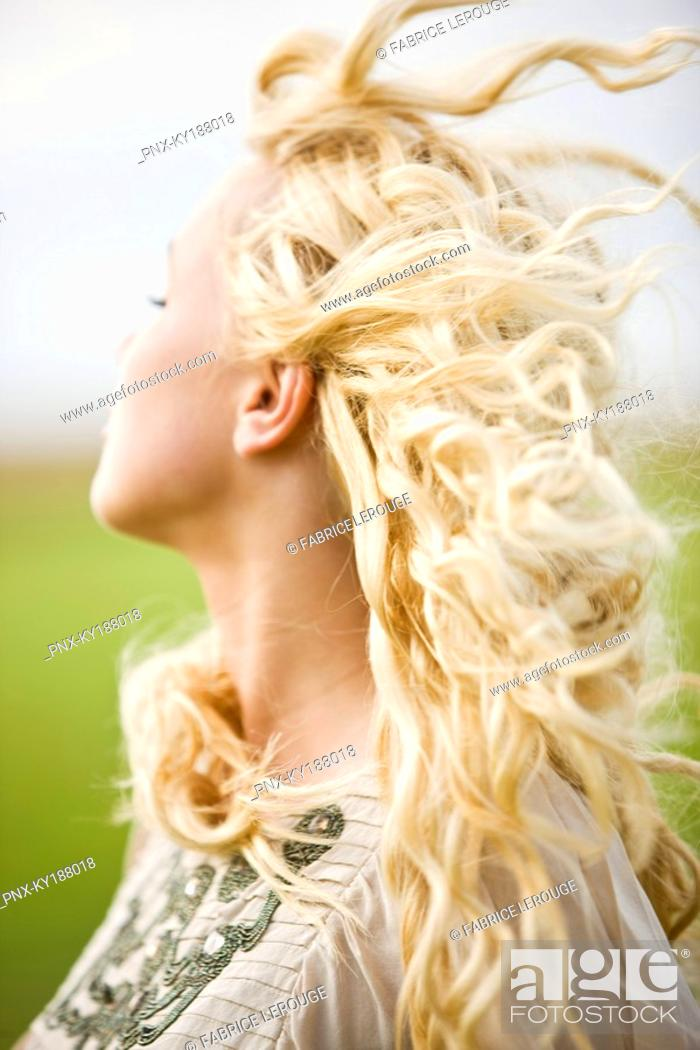 Stock Photo: Portrait of a young woman, hair in the wind.