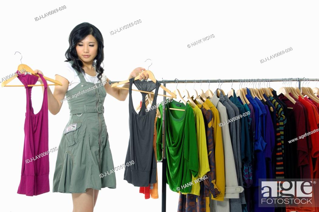Stock Photo: Woman selecting tops in a clothing store.