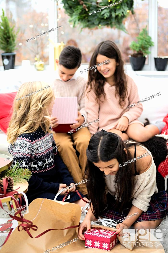 Stock Photo: Four children unwrapping presents.