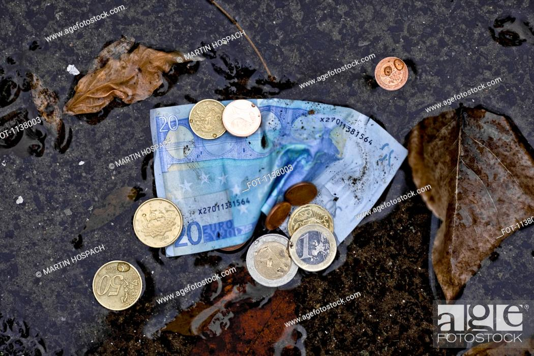 Stock Photo: A twenty euro banknote and euro coins in a puddle.