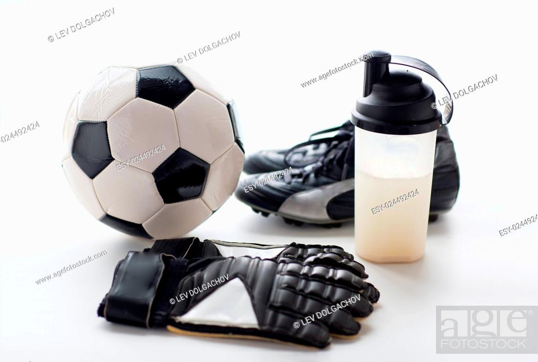Stock Photo: sport, soccer and sports equipment concept - close up of ball, football boots, goalkeeper gloves and protein shake bottle with drink.