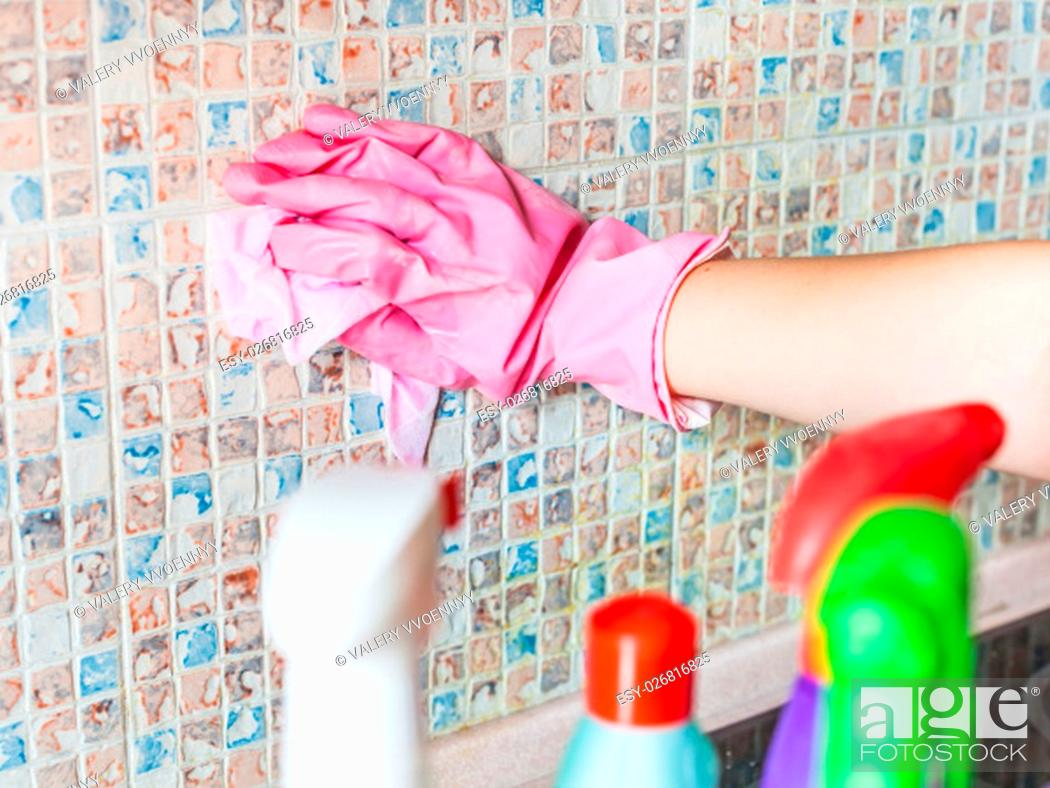 Stock Photo: House cleaning - hand in glove washes ceramic tiles on kitchen wall.