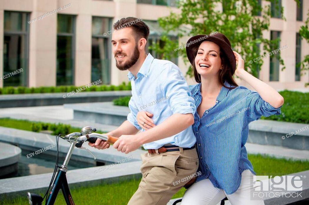 Stock Photo: Young couple sitting on a bicycle.