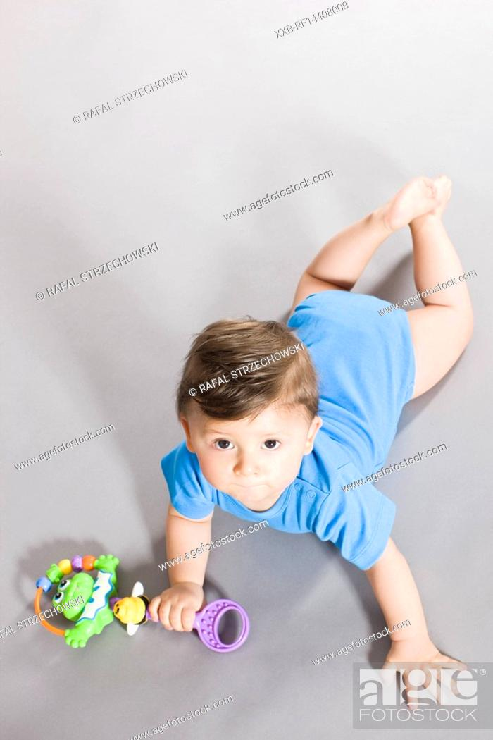 Stock Photo: Baby crawling on floor with toy.