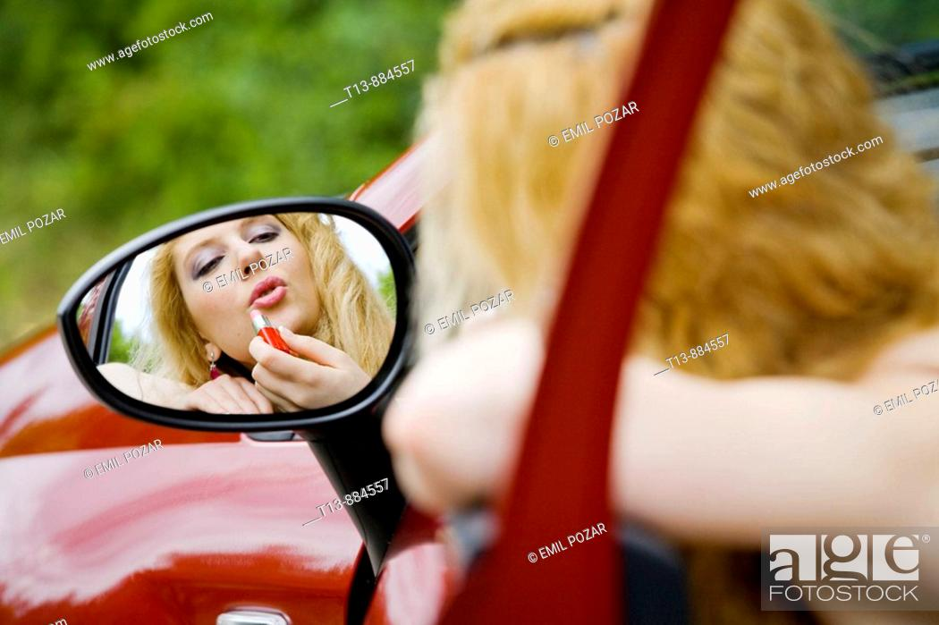 Stock Photo: Applying make-up in car's outside mirror.